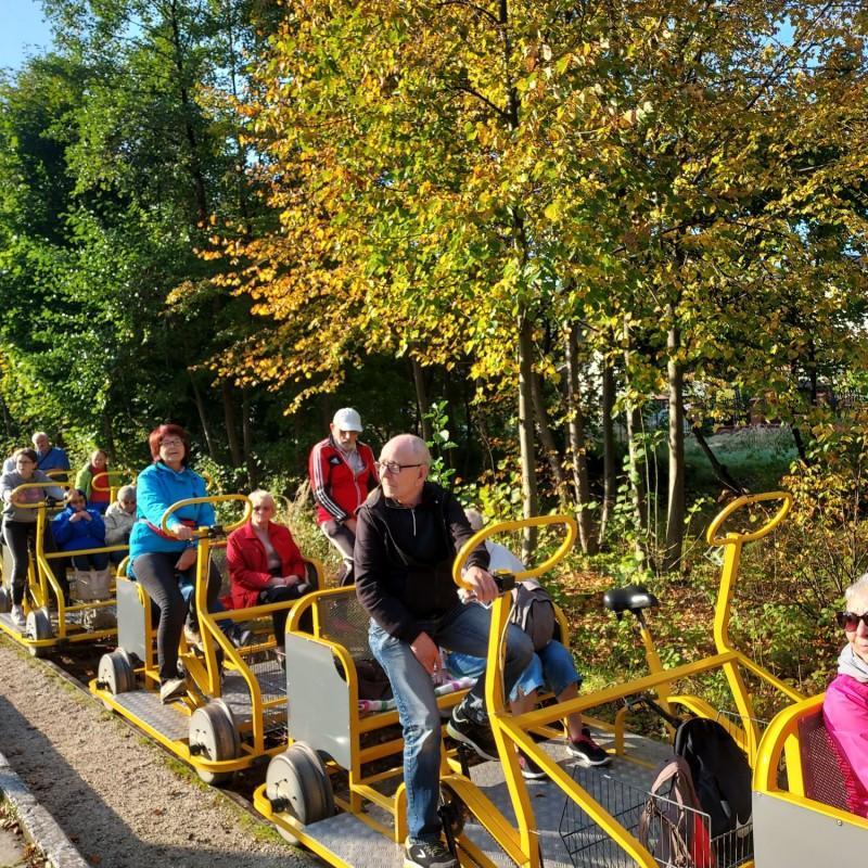 Zdjęcie nr 5: Grupa osób jadąca na żółtych drezynach. W tle jesienne liście.