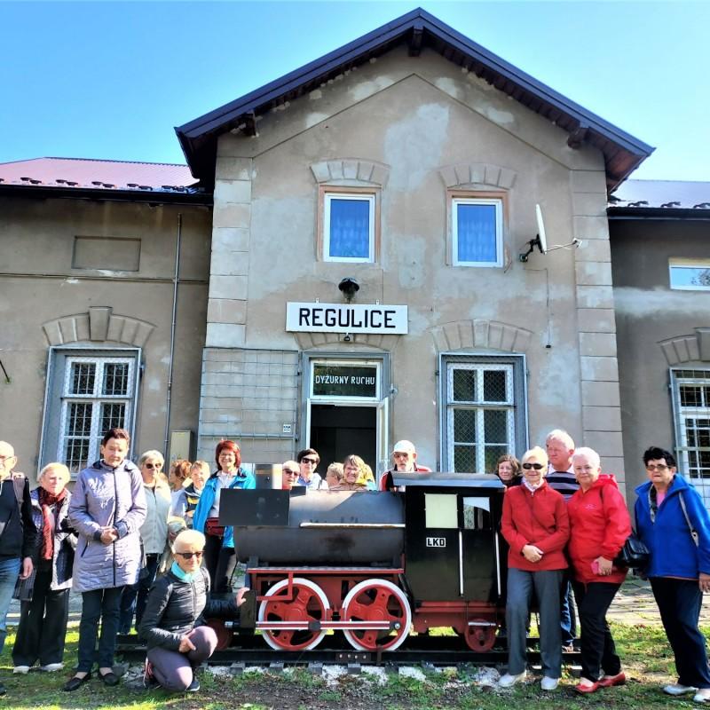 Zdjęcie nr 2: Grupa uśmiechniętych ludzi stojących przy atrapie lokomotywy przed budynkiem dyżurki ruchu kolejnowego z napisanem Regulice.