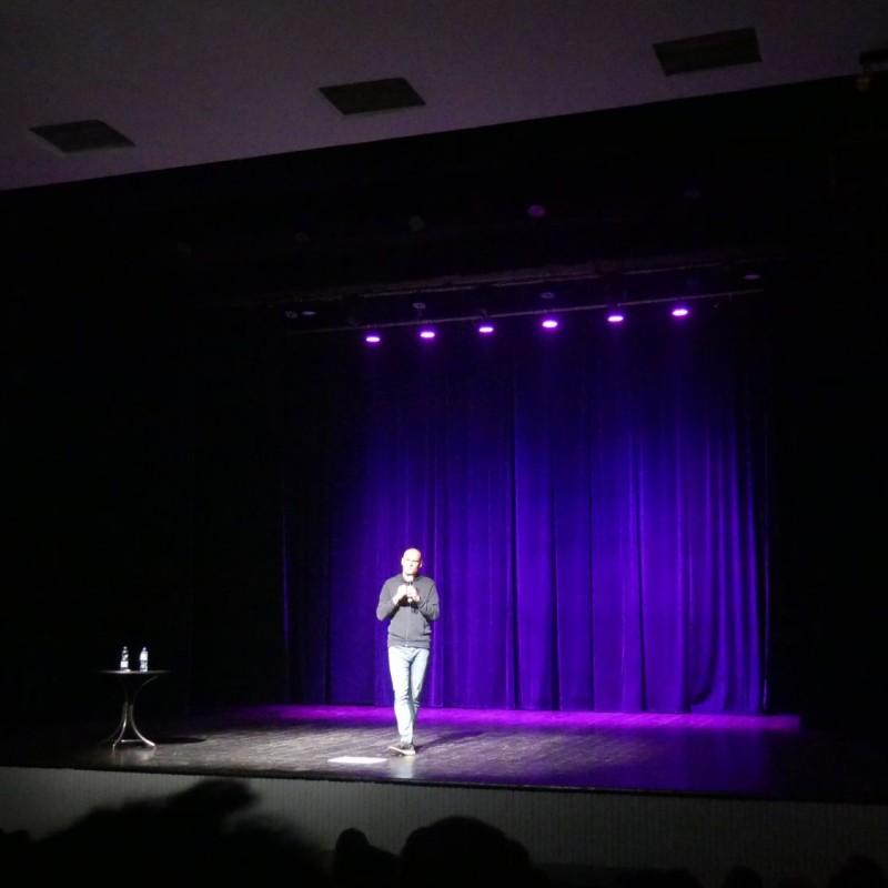 Osoba stojąca na środku sceny, oświetlona przez fioletowe światło.