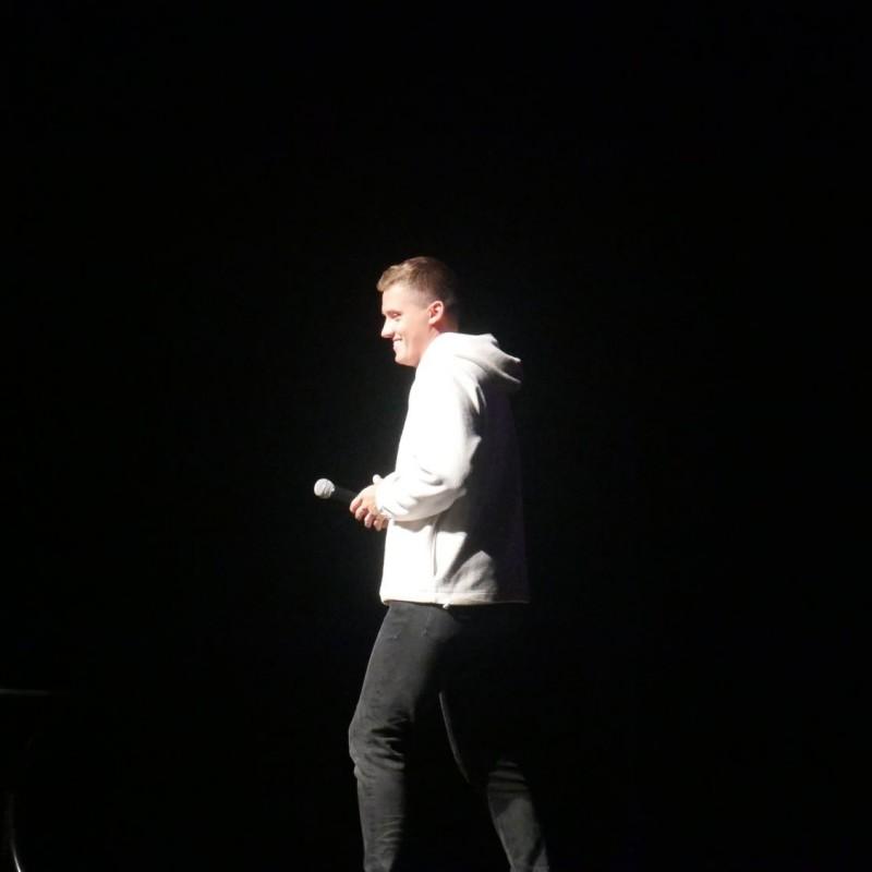 Uśmiechnięty chłopak w białej bluzie, chodzi po scenie.