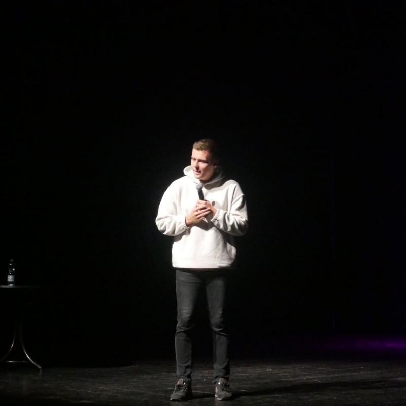 Chłopak w białej bluzie, stoi na scenie, opowiadając żarty.