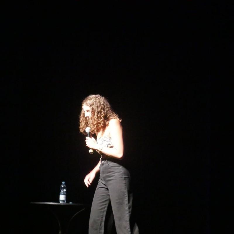 Kobieta na scenie z mikrofonem, sięga po, znajdującą się obok, butelkę wody.