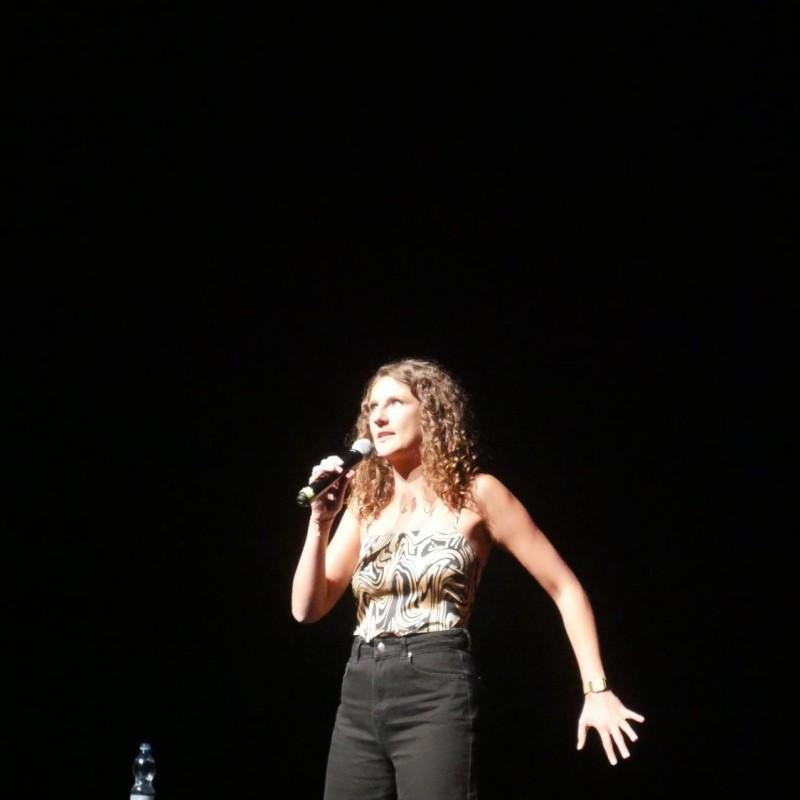 Kobieta w kręconych włosach stoi na scenie. W prawej ręce trzyma mikrofon, natomiast drugą ma wyciągnięta w tył.