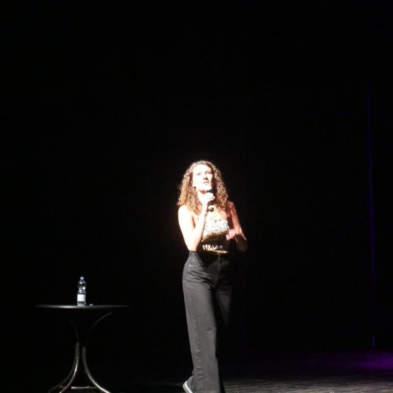 Kobieta przechadza się po scenie z mikrofonem w prawej dłoni. Za nią znajduje się mały stolik z butelką wody.